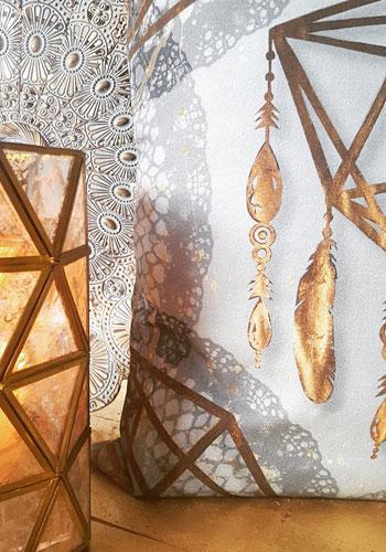 Kudde från Van Asch med tryck som glimmar som guld. Fat och ljuslyktar matchar inredningen.