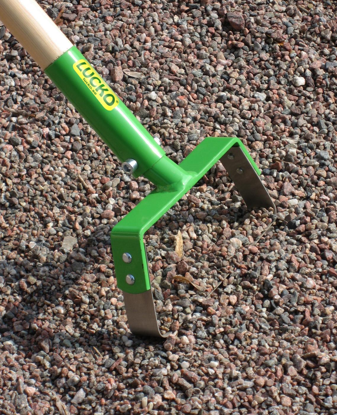 Pendelhacka rensar ogräs  på grusgång