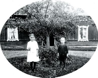 Greta och Harald Persson framför barndomshemmet Simmesgården 1920. Bilden finns också nedan!