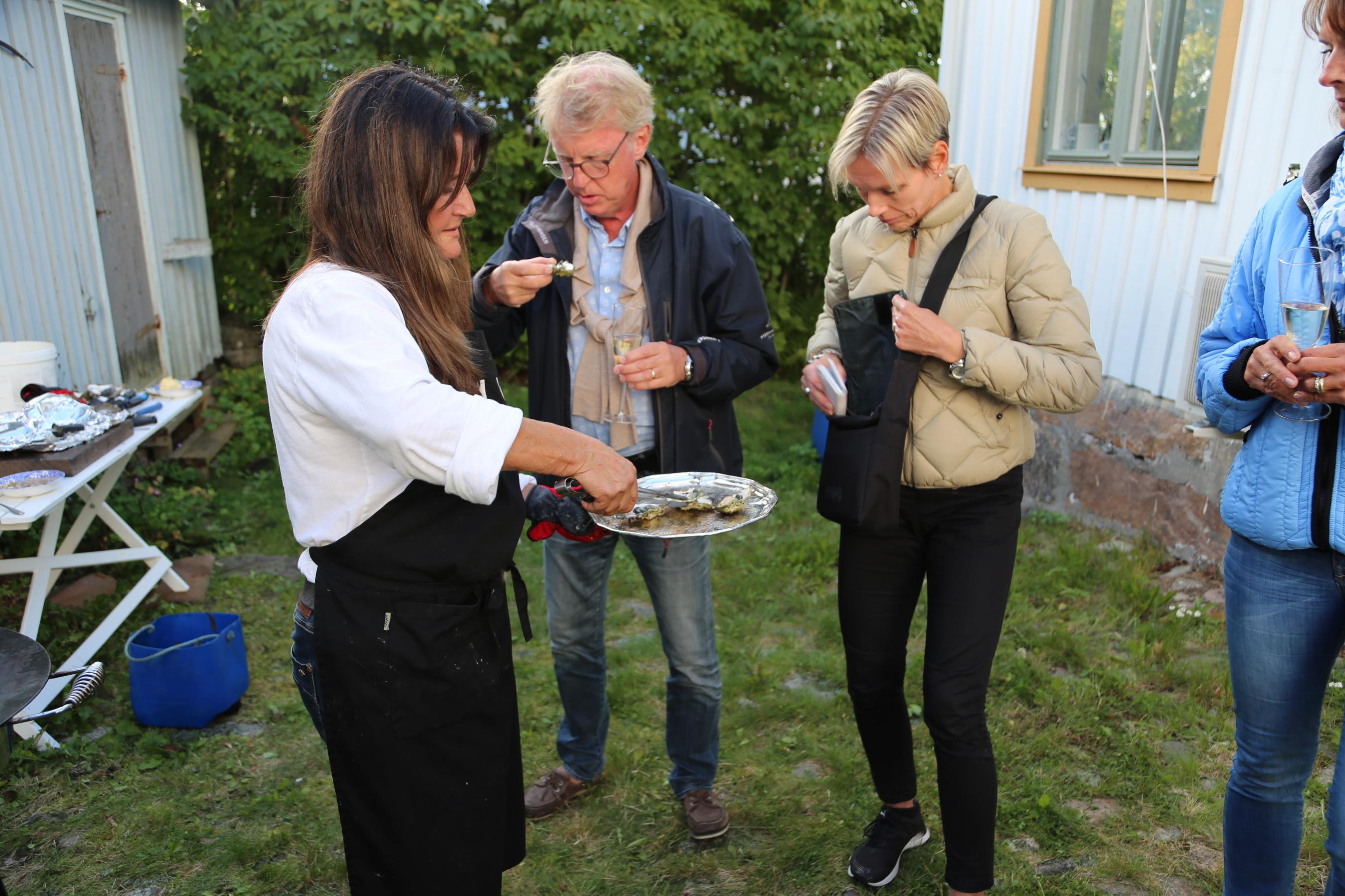 Åsa serverar ostron i trädgården till Everts Hus.