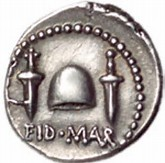 """Tyrann? Mynt som caesarmördaren Marcus Brutus lät prägla. EID MAR är en förkortning med äldre stavning av Idus Martiae, romarnas benämning på den 15 mars, dagen då mordet utfördes. En pileus, den mössa som slavar fick ta på sig när de frigavs, flankeras av knivarna som användes för att döda """"tyrannen"""". Symboliken med slaven som får sin frihet kan inte vara tydligare: staten hade befriats från tyrannen."""