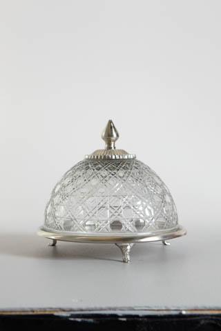 Glasklocka med silverfärgat fat på små ben. 21 cm hög, fatets diameter 23 cm