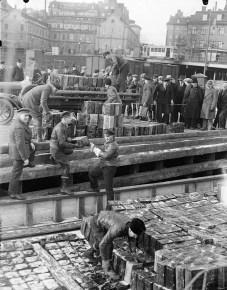 Smuggelsprit lossas i Stadsgårdshamnen efter det stora spritbeslaget vid Sundskär, natten till den 10 mars 1930. Tull och polis beslagtog mer än 20000 liter sprit.  Foto Axel Malmström (1872 - 1945)