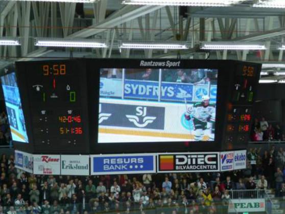 Media-kub från Elitseriearenan i Ängelholm, Lindab Arena där Rögle spelar sina hemmamatcher. Mediakuben består av fyra stycken fullvideo-displayer med fyra stycken numeriska Omega-displayer.
